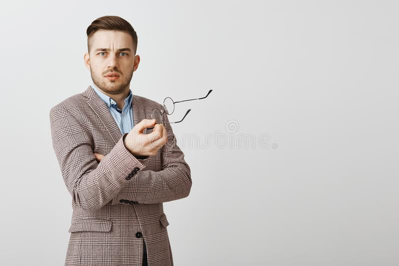 Waist-up shot of intense confused good-looking male entrepreneur in stylish jacket taking off glasses and gesturing with. Them near gray background staring stock photo