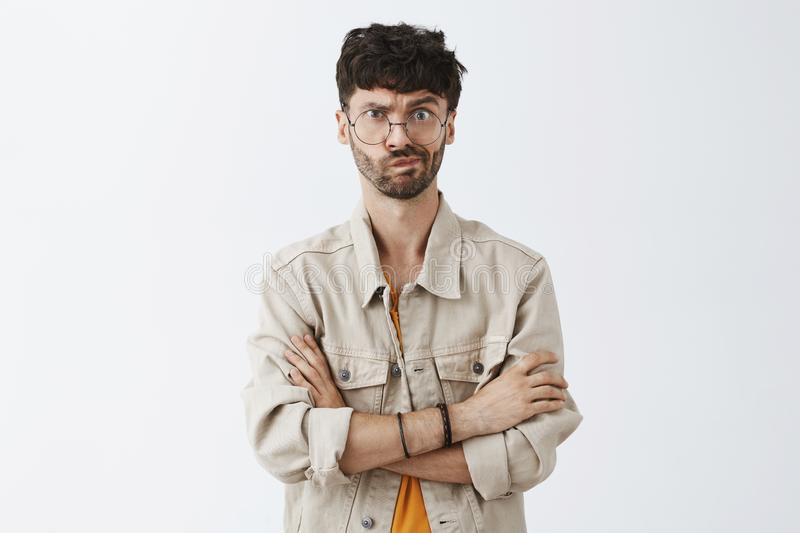 Waist-up shot of intense dissatisfied handsome mature caucasian guy with beard in beige jacket holding hands crossed on stock photos