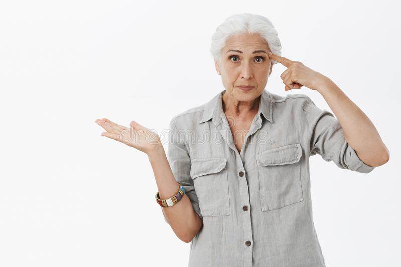 Waist-up shot of irritated smart elderly woman being with son making stupid mistake rolling finger near temple. Pursing lips from annouance and pointing left royalty free stock photography