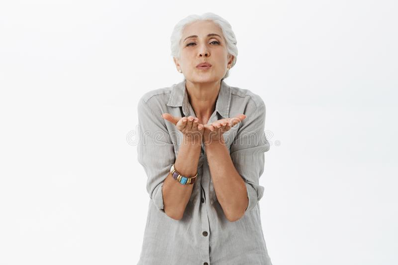 Waist-up shot of kind and cute loving grandmother with gray hair folding lips blowing kiss via air with palms near mouth stock photos