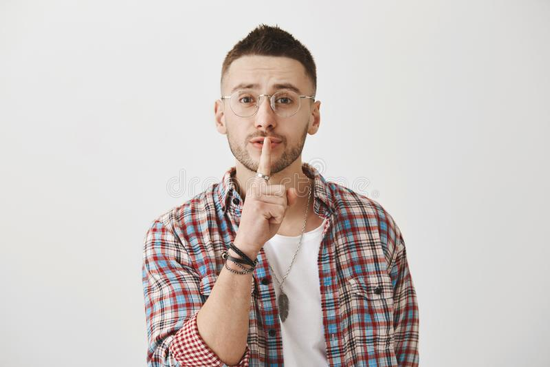 Waist-up shot of kind friendly man in glasses, saying shush with slight smile, holding index finger over mouth, asking stock image