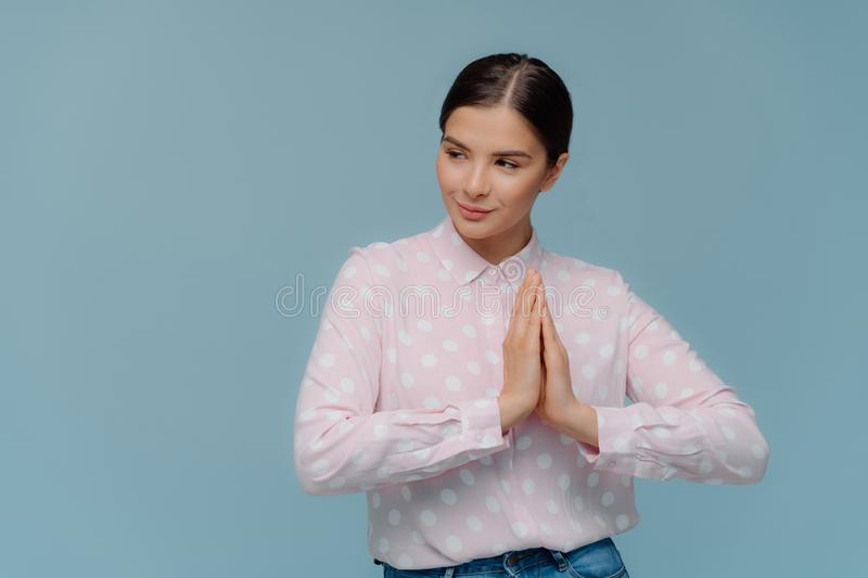 Waist up shot of lovely woman presses palms together, prays indoor, focused away, wears polka dot shirt, has serious thoughtful stock photo