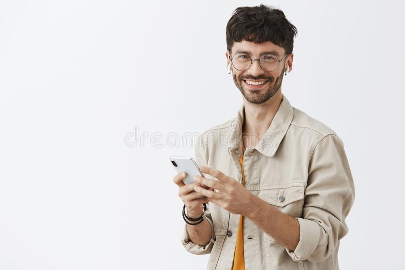 Waist-up shot of modern happy and joyful dark-haired man with beard in glasses listening music in wireless earphones and royalty free stock photos