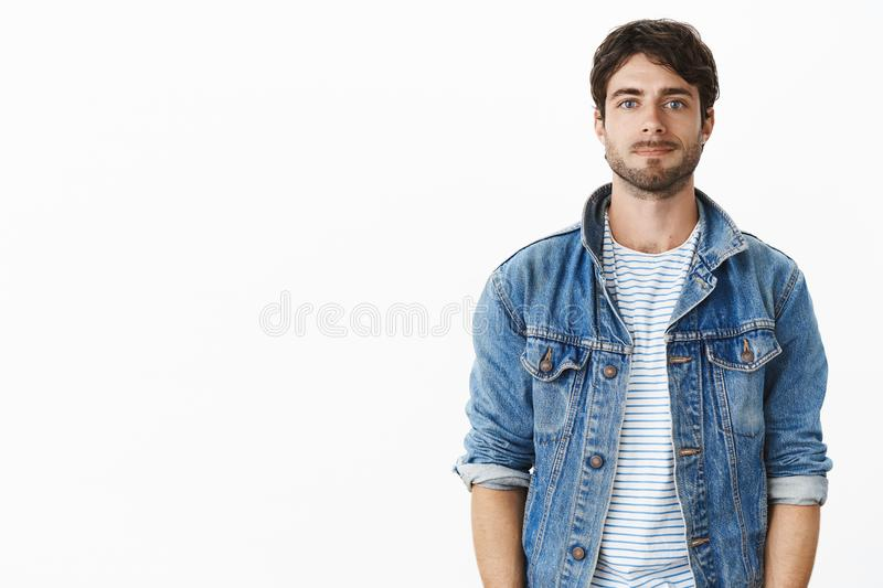 Waist-up shot of nice handsome guy in stylish denim jacket over striped t-shirt smirking shy and awkward as standing stock image