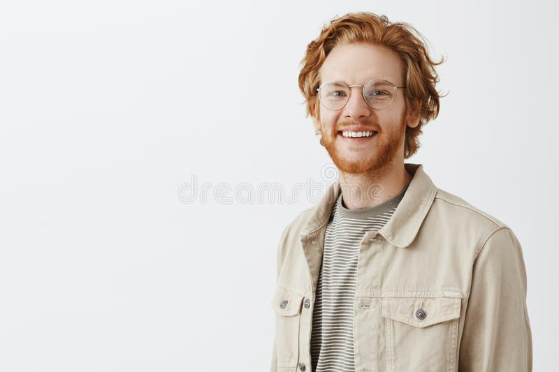 Waist-up shot of pleasant handsome redhead mature guy with beard in transparent glasses and beige jacket over t-shirt royalty free stock photography