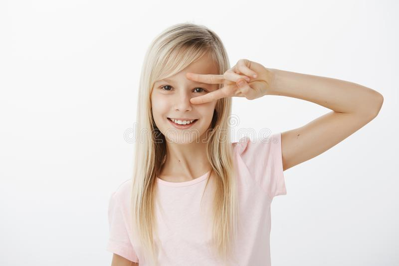 Waist-up shot of positive charming child with blond hair in casual outfit, showing victory or peace gesture over eye and. Smiling happily, dancing or having fun stock images