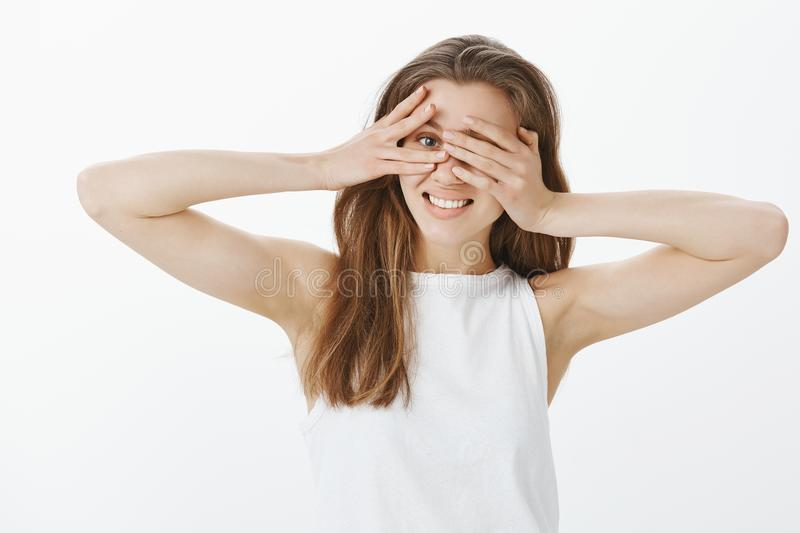 Waist-up shot of positive charming european woman with fair hair, covering eyes with palms, peeking through fingers at. Camera, smiling broadly, waiting for royalty free stock photos