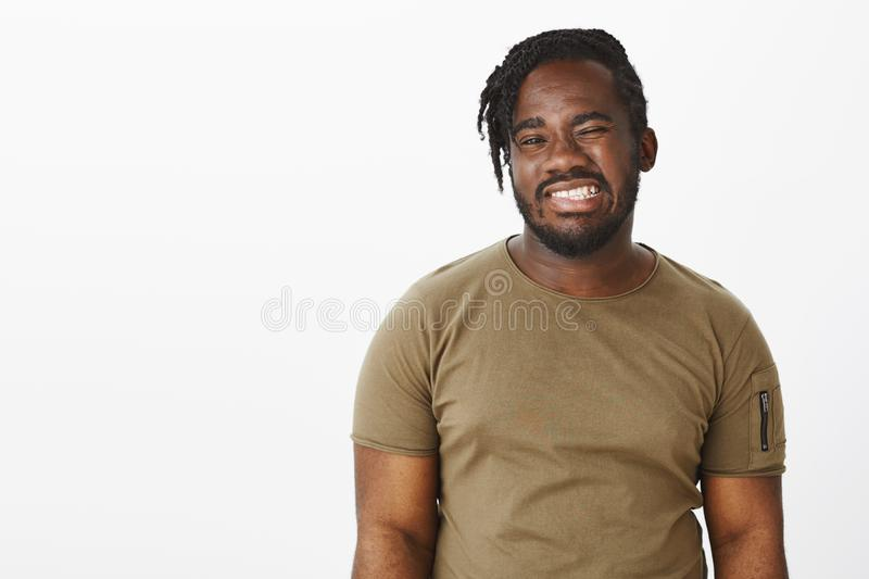 Waist-up shot of positive happy african-american man with beard, winking and smiling broadly with perfect white teeth. Feeling joyful while hanging out over stock photos