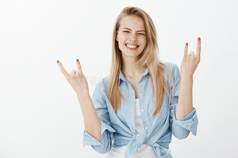 Waist-up shot of positive happy european blond woman in trendy clothes, raising hands and showing rock n roll sign. Smiling broadly, being satisfied while royalty free stock photos