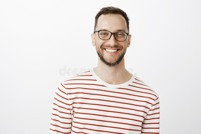 Waist-up shot of relaxed good-looking positive guy in glasses, smiling broadly and gazing at camera while talking with. Friend, standing against gray background royalty free stock image