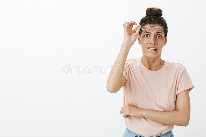 Waist-up shot of scared worried and insecure young silly woman taking off glasses biting lower lip and frowning, feeling royalty free stock image