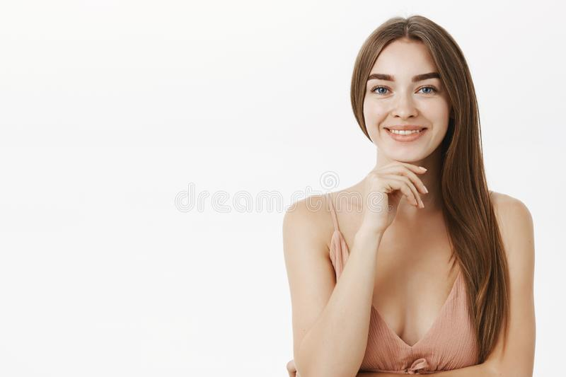 Waist-up shot of sensual and feminine brunette in cute beige dress holding hand on chin and smiling broadly having pure stock photography
