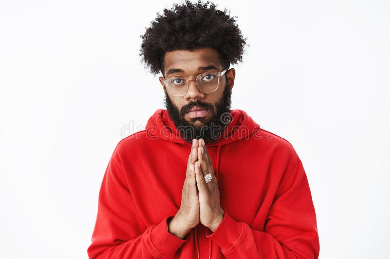 Waist-up shot of serious-looking african guy with beard holding hands in pray as asking for help being in need having. Troubles praying begging for favour stock image