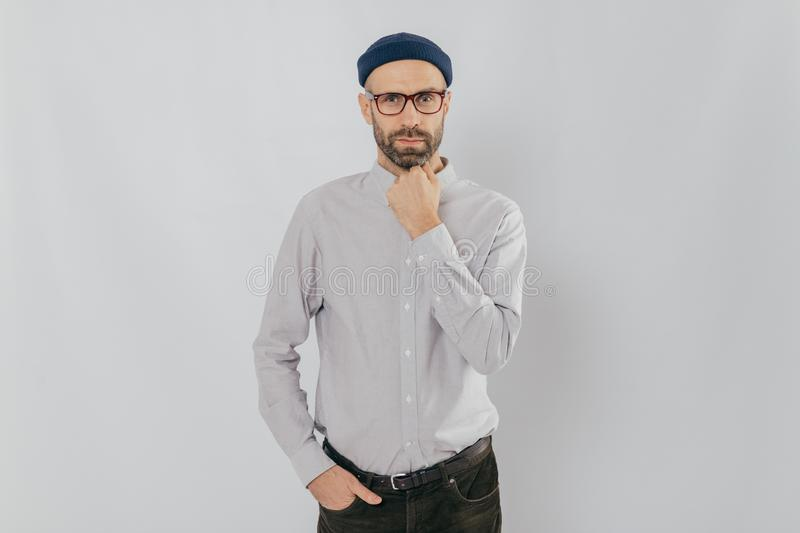 Waist up shot of serious man keeps one hand under chin, other in pocket, has stubble, wears hat, white shirt, trousers, isolated royalty free stock photography