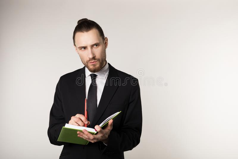 Waist up shot of serious unshaven businessman in black suit that attentively listens to his business partner and takes stock photography