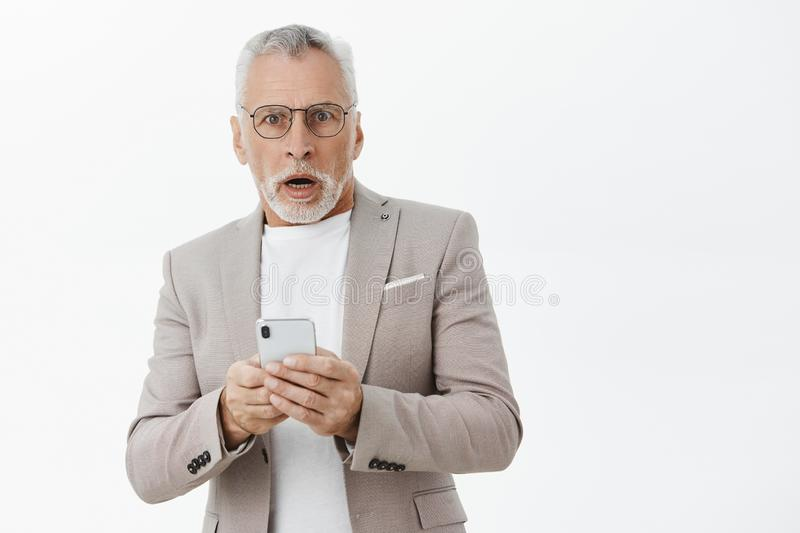 Waist-up shot of shocked senior man in suit and glasses gasping opening mouth from worry and surprise holding smartphone. Receiving bad news looking concerned stock image
