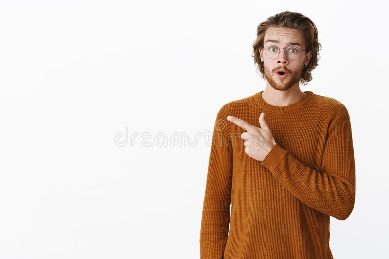Waist-up shot of shocked and stunned confused young man in glasses and sweater raising eyebrow in questioned expression stock photo