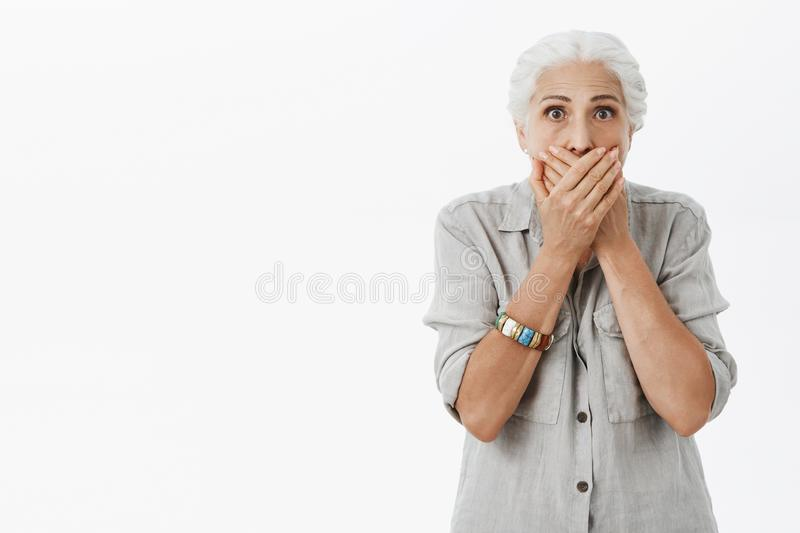 Waist-up shot of shocked and stunned elderly woman in casual shirt with grey hair gasping covering mouth with both palms stock image