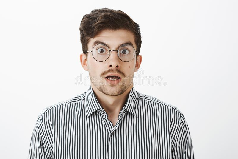 Waist-up shot of shocked surprised funny bearded guy with moustache in round transparent eyewear, dropping jaw, saying royalty free stock photo