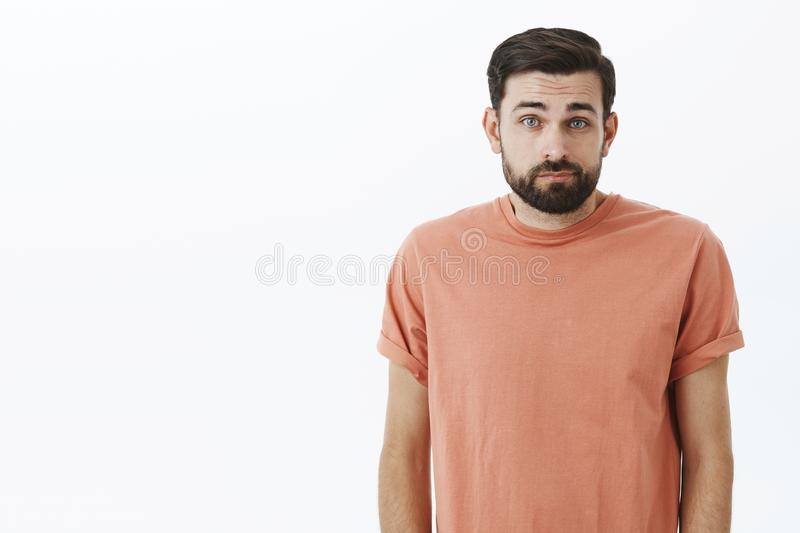 Waist-up shot of silly insecure and unconfident cute bearded guy in casual t-shirt shrugging looking gloomy and unaware. Being clueless how deal with life stock photography