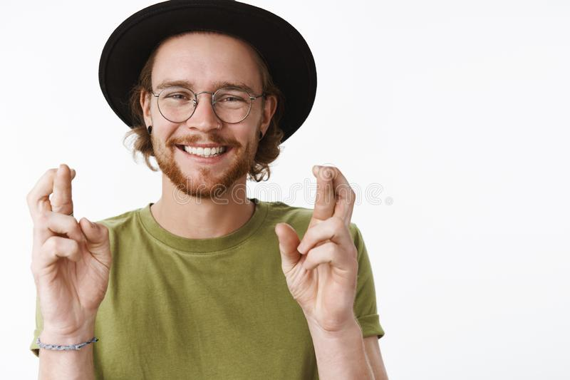 Waist-up shot of sincere happy and kind young bearded male traveler making hopes or wish with raised hands and crossed stock images