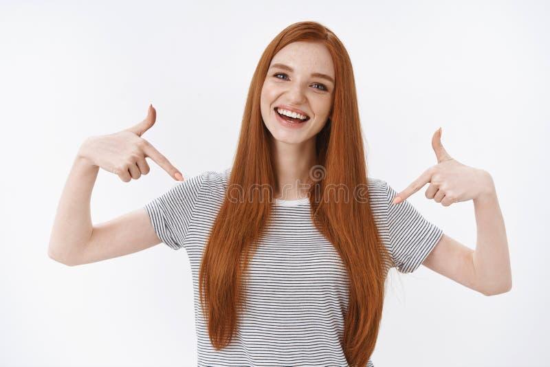 Waist-up shot skillful good-looking joyful smiling redhead woman blue eyes wearing summer t-shirt pointing index fingers. Herself bragging achievement telling royalty free stock photo