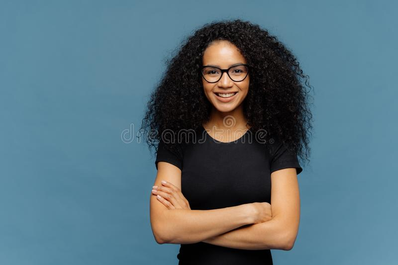 Waist up shot of smiling Afro American woman has arms folded, wears spectacles and casual black t shirt, enjoys nice conversation. With interlocutor, poses over stock image