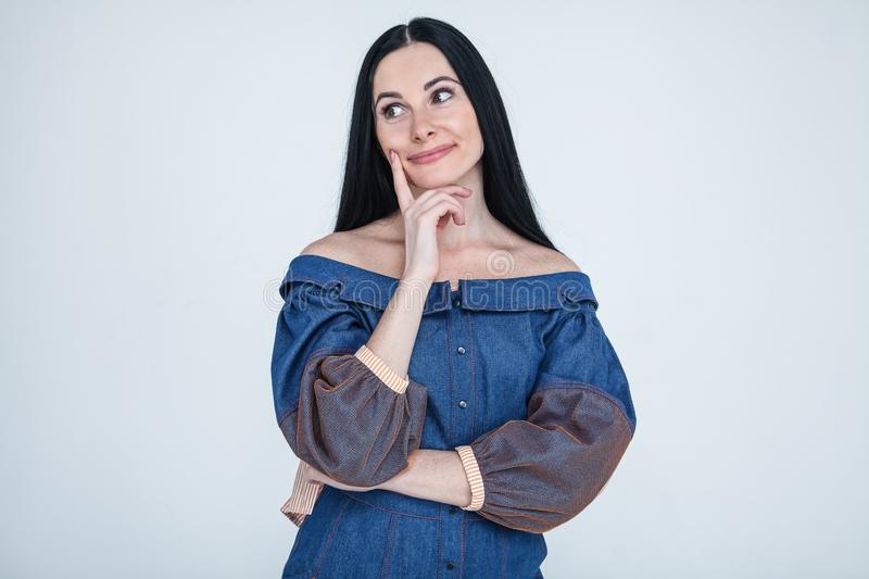 Waist-up shot of spaced out silly glamour girl with brunette hair in jeans elegant dress touching chin as staring at camera with stock photo