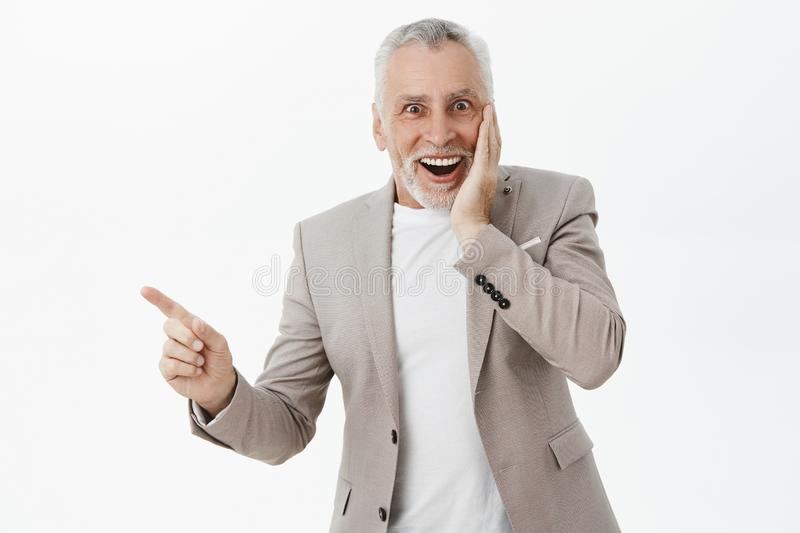 Waist-up shot of speechless delighted and surprised handsome elegant grandfather in stylish suit pressing hand to cheek stock photo