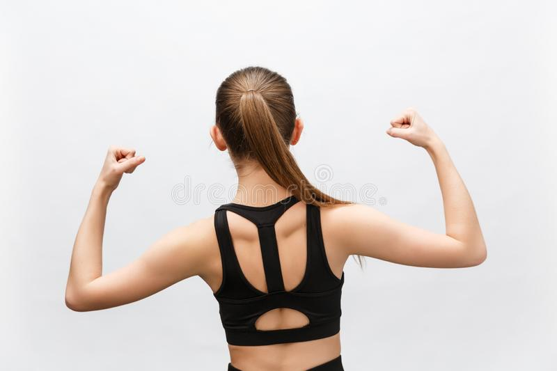 Waist up shot of sporty woman raises hand to show her muscles, feels confident in victory, looks stong and independent royalty free stock photography