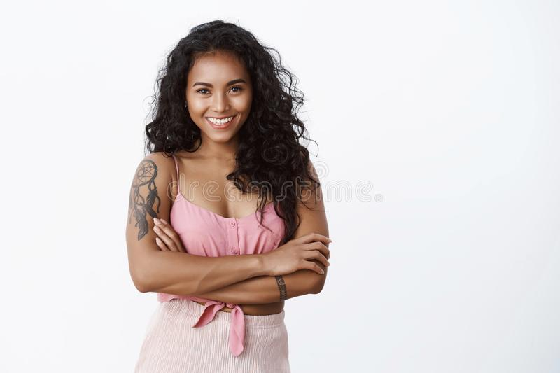 Waist-up shot successful happy elegant african-american curly-haired woman with tattooed arms, cross hands chest and. Smiling toothy, looking confident and royalty free stock photo
