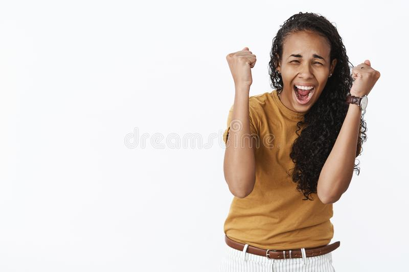 Waist-up shot of super excited astonished and happy joyful young african american woman raising clenched fists in royalty free stock photo