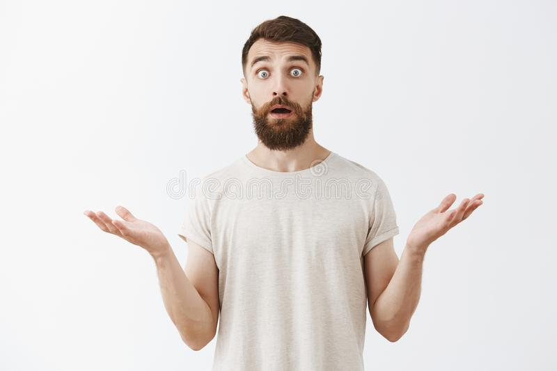 Waist-up shot of surprised and amazed good-looking stylish bearded male raising eyebrows shrugging with hands spread. Aside cannot understand what happened royalty free stock photos