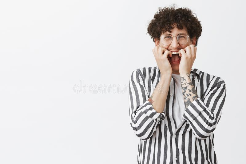 Waist-up shot of timid and insecure funny jewish guy with dark curly hair and moustache in glasses and striped shirt stock images