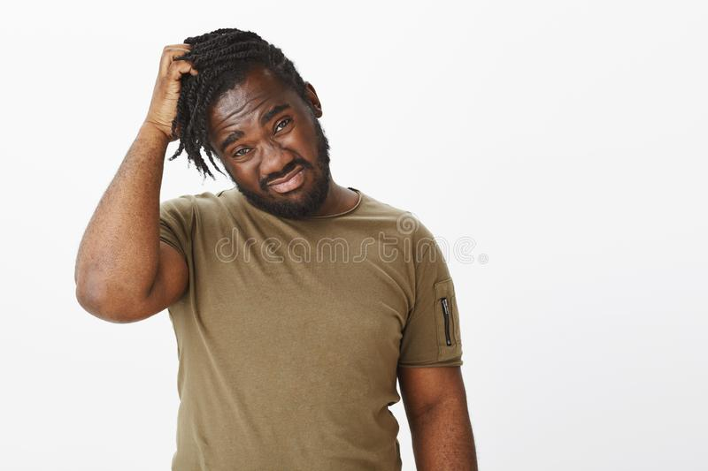 Waist-up shot of unsure and uncertain african-american guy scratching head and staring displeased at camera, being. Confused or stuck while making decision royalty free stock photography