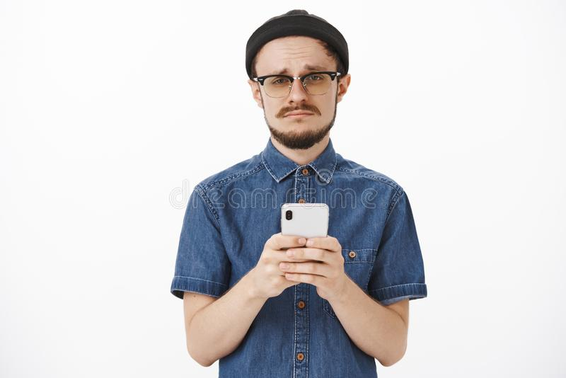 Waist-up shot of upset gloomy cute bearded guy in black beanie and glasses making sad face and frowning holding. Smartphone expressing jealousy or regret stock photo