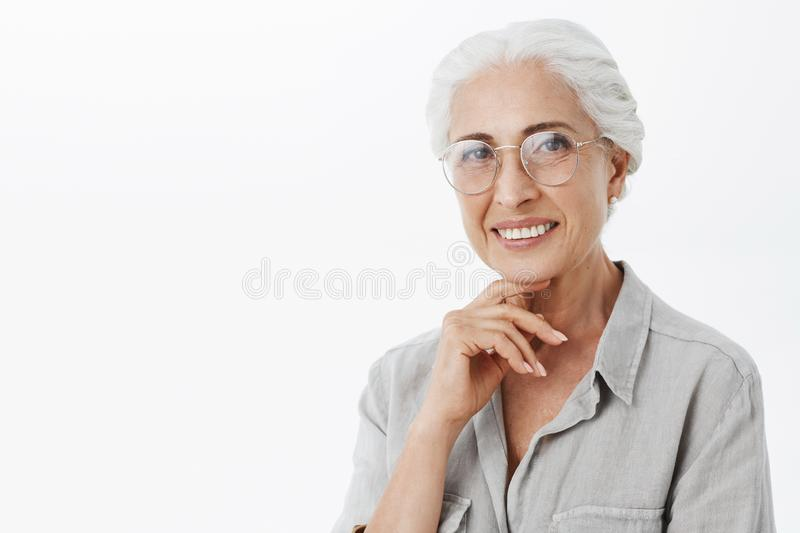 Waist-up shot of wise and pleased carefree kind grandmother in glasses with white hair holding hand on chin in. Thoughtful and delighted pose smiling broadly in stock image