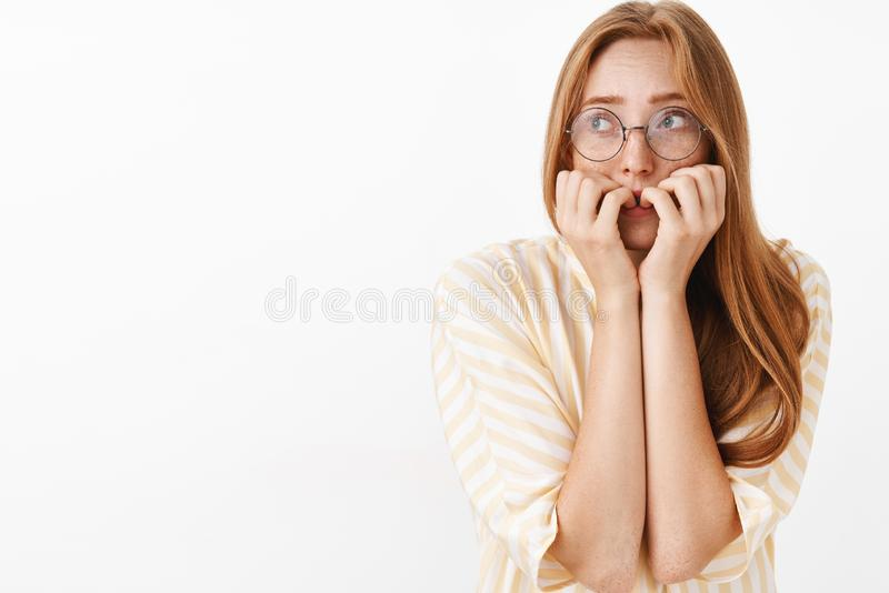 Waist-up shot of worried panicking cute and timid insecure redhead girl in glasses looking up trembling from fear biting. Fingernails shaking feeling scared stock image