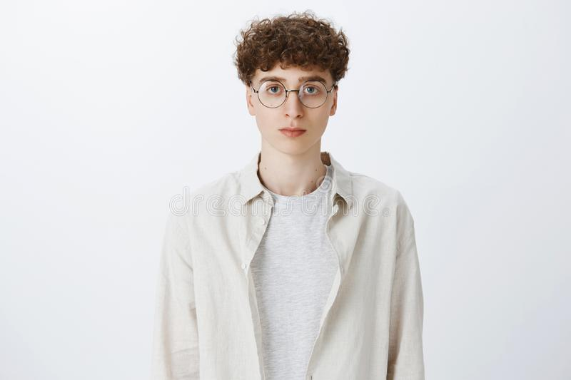 Waist-up shot of young attractive and stylish hipster guy with curly hair in round glasses and shirt looking strict at royalty free stock image
