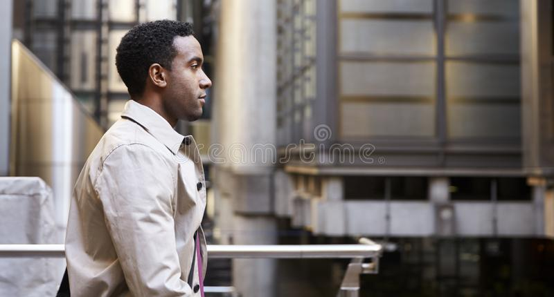 Waist up side view of young black businessman walking past modern architecture in there city, London UK royalty free stock photos