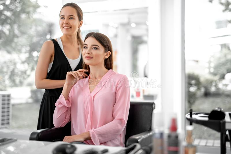 Beautiful woman is sitting in armchair near her makeup artist. Waist up of smiling lady looking in the mirror while female stylist standing nearby royalty free stock photography
