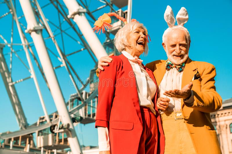 Happy old man giving hand to his wife outdoors stock photos