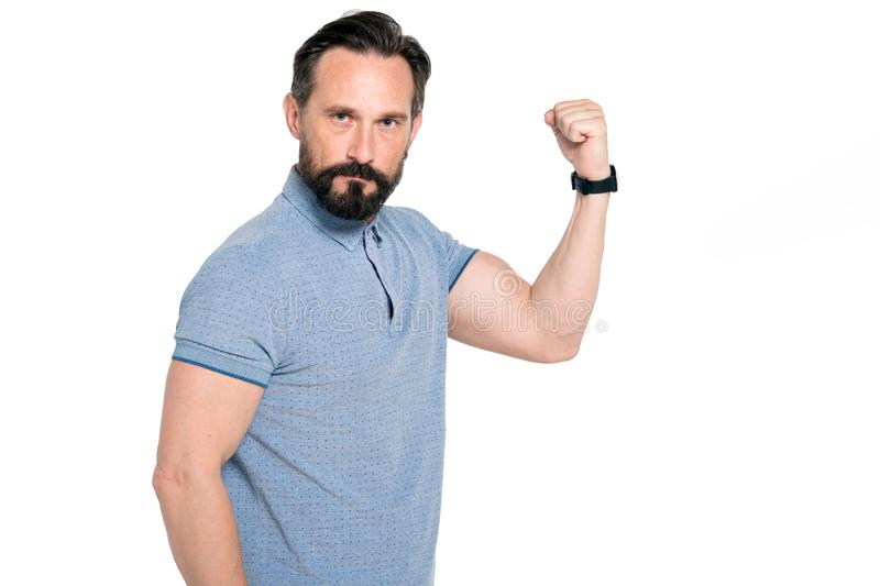 Waist up of strong muscular man demonstrating his biceps. Strong middle aged bearded man being serious while showing his biceps and expressing confidence on his royalty free stock images