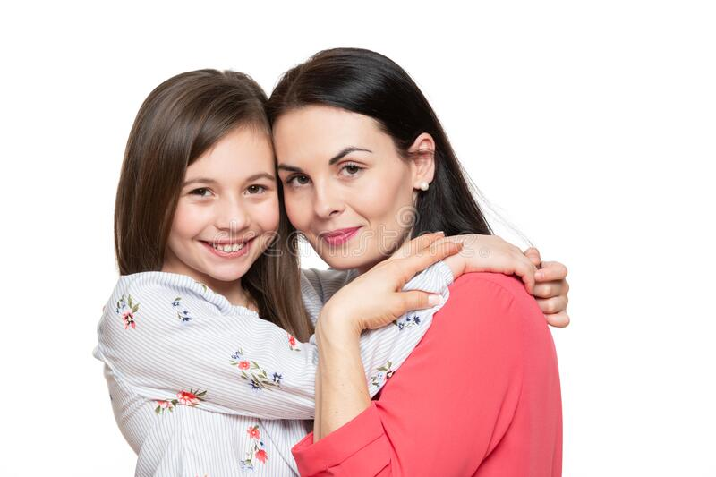 Waist up studio portrait of cute and playful schoolgirl embracing her mother. Happy smiling family background. Waist up studio portrait of cute and playful stock photos