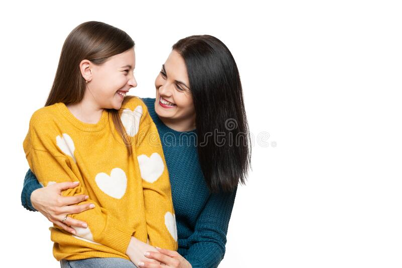 Waist up studio portrait of a mother and young daughter face to face laughing. Happy family laughing background. Waist up studio portrait of a mother and young royalty free stock photography