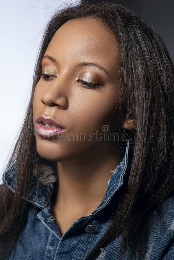 Waist up studio shot of the attractive woman of the mulatta with make up wearing jeans dress stock image