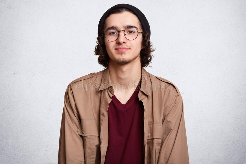 Waist up studio shot of delighted calm guy standing straight, looking directly at camera, wearing beige jacket, red sweatshirt and stock photography