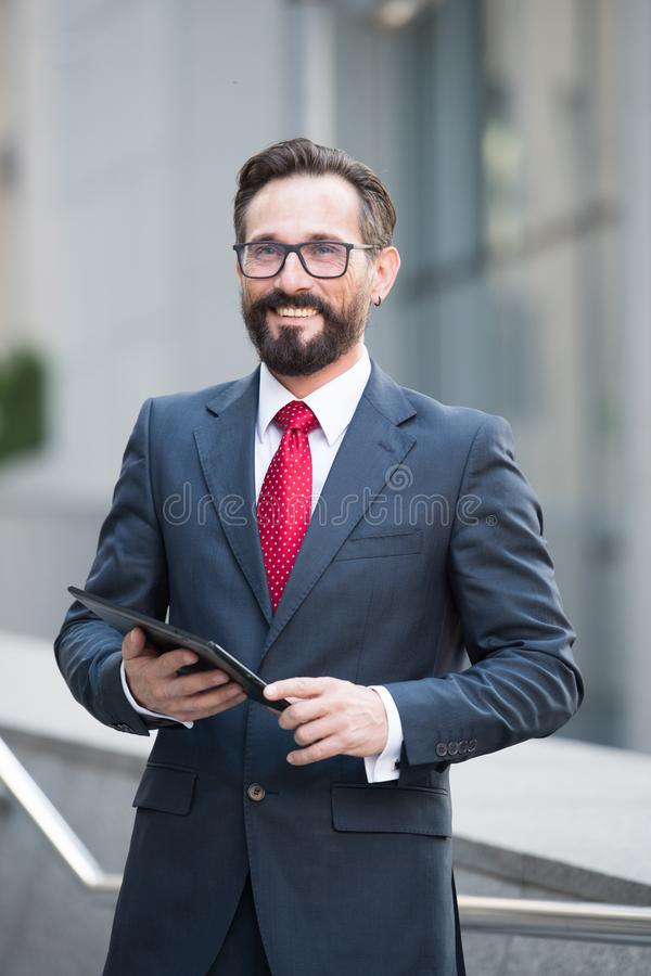 Waist up of successful banker with a tablet in hand. Positive affluent banker wearing grey suit and looking away while holding digital tablet in hand and smiling royalty free stock photography