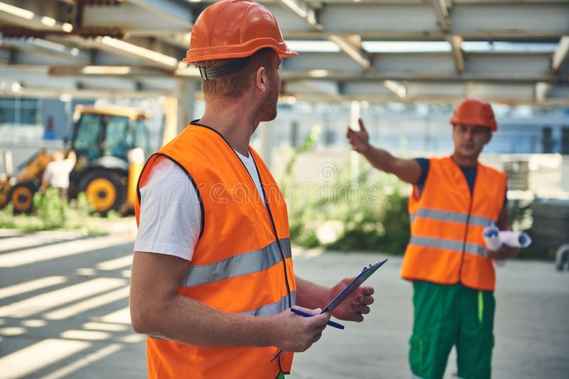 Workers in orange form are communicating at the construction site stock image