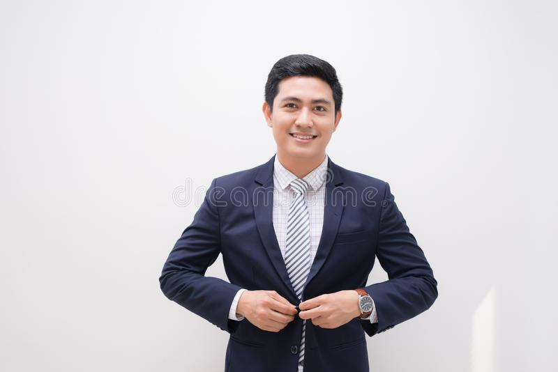 Waistup portrait of young smiling handsome businessman putting on suit jacket looking aside isolated on white royalty free stock photography